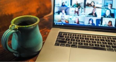 Mug next to computer with meeting