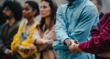 Multicultural group holding hands together